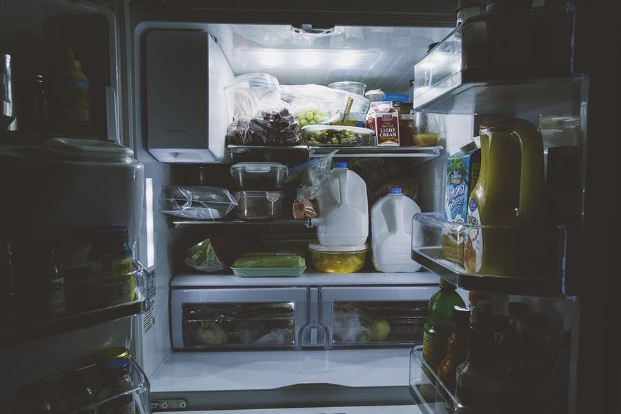 Загружает купленные продукты в холодильник как попало